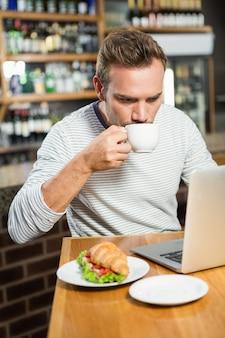 Uomo bello che per mezzo del computer portatile e mangiando un caffè