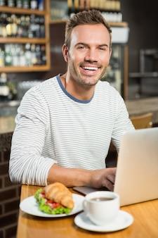 Uomo bello che per mezzo del computer portatile e mangiando un croissant