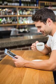 Uomo bello che per mezzo della compressa e mangiando caffè