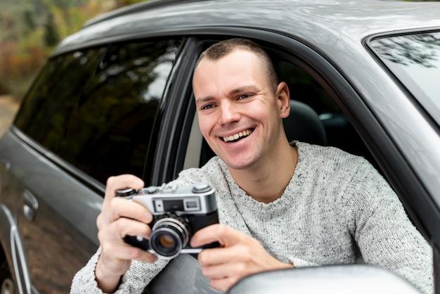 Uomo bello che per mezzo di una macchina fotografica d'annata