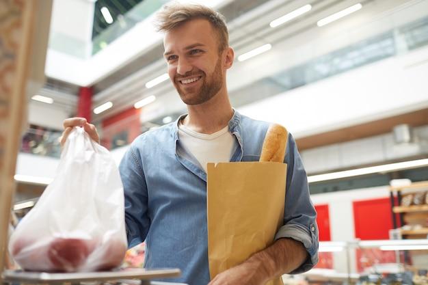 Uomo bello che pesa i pomodori in supermercato