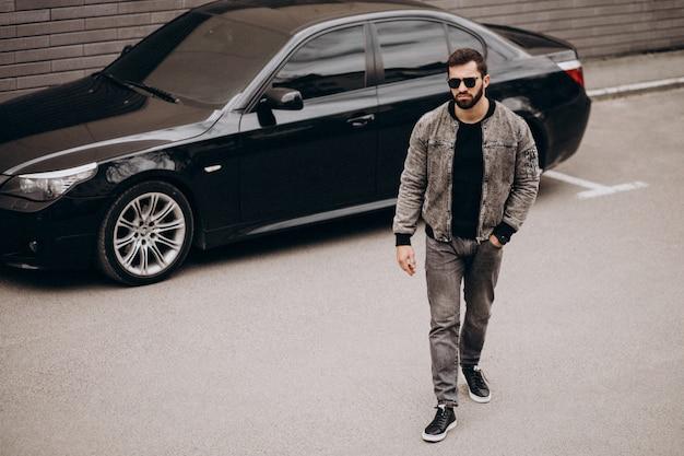 Uomo bello che posa in macchina nella via