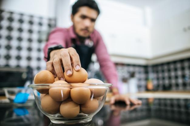 Uomo bello che prepara le uova in cucina. è tempo di cucinare.