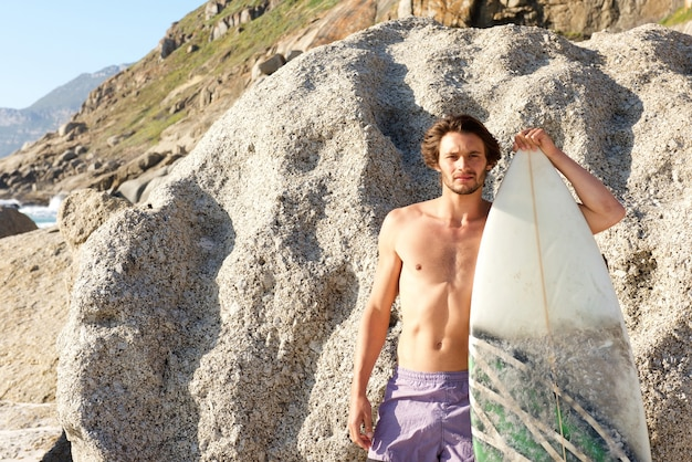 Uomo bello che propone con il surf in spiaggia