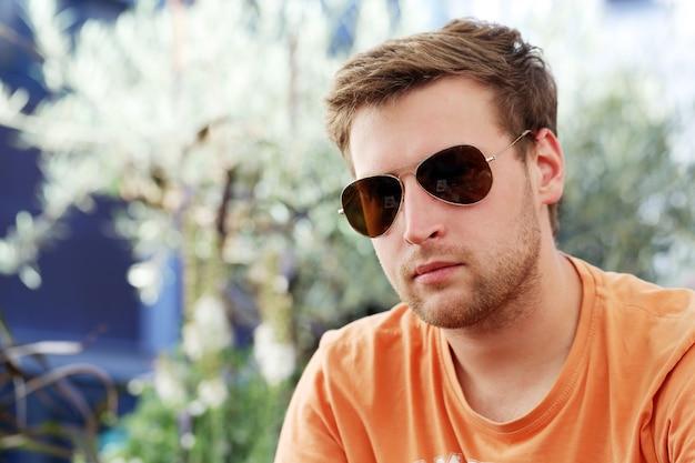 Uomo bello che propone in occhiali da sole