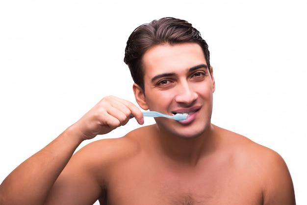 Uomo bello che pulisce i suoi denti isolati su bianco