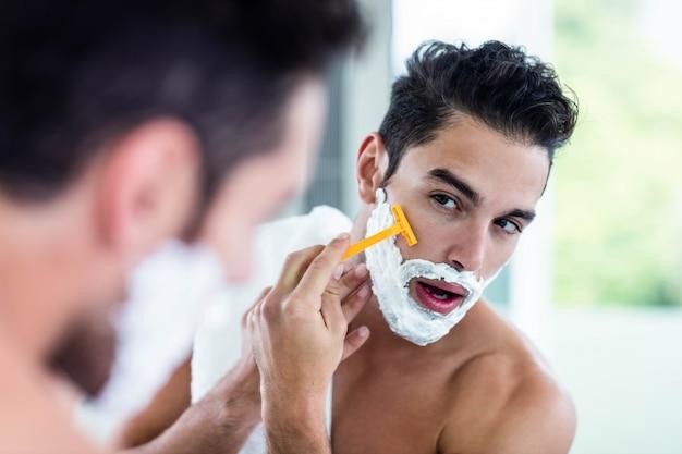 Uomo bello che rade la sua barba in bagno