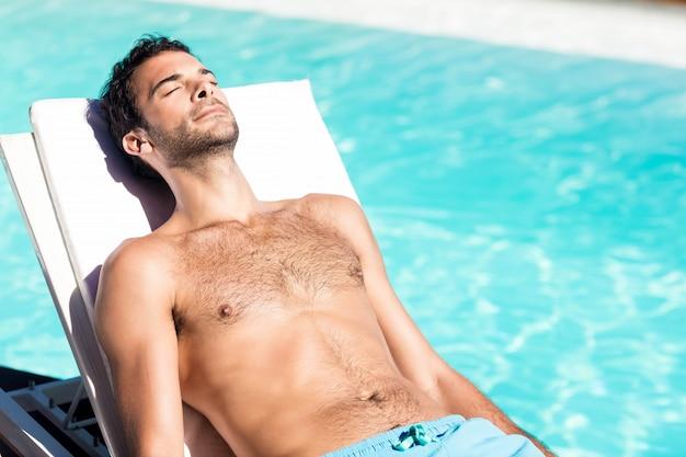 Uomo bello che riposa sulla sedia a sdraio a bordo piscina