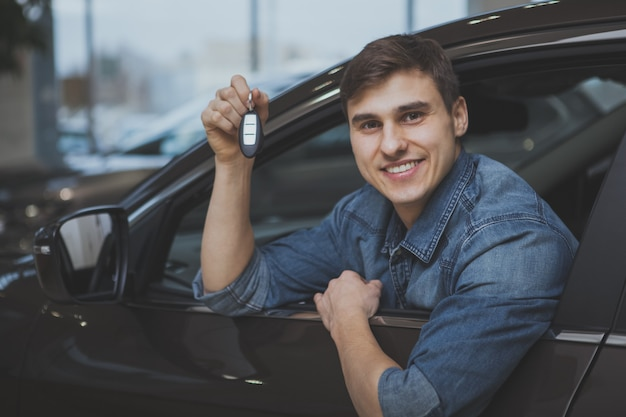 Uomo bello che sceglie nuova automobile da comprare