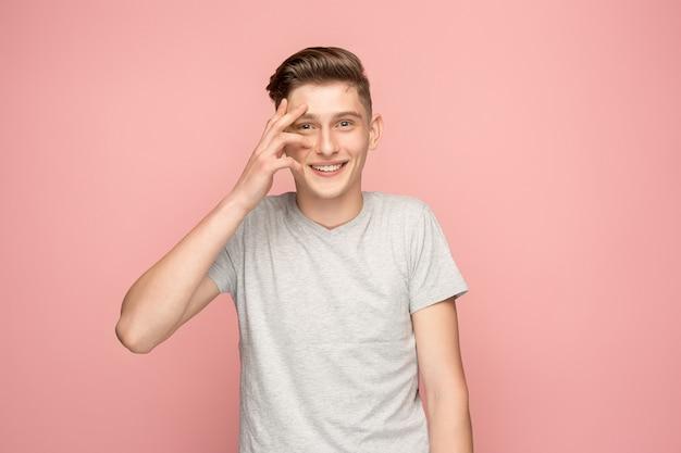 Uomo bello che sembra sorpreso isolato sul rosa