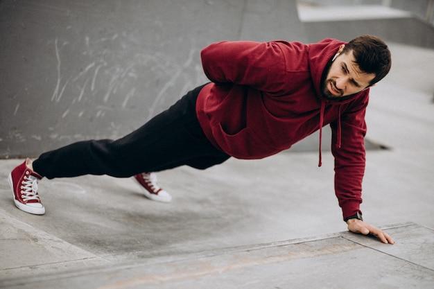 Uomo bello che si esercita nel parco nell'usura di sport