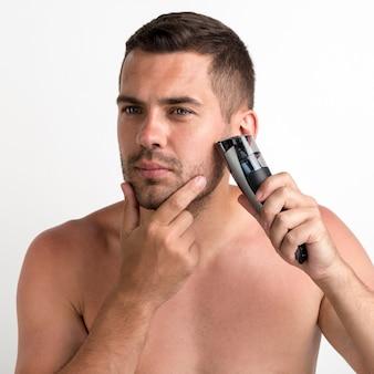 Uomo bello che si rade con il regolatore elettrico isolato su fondo bianco