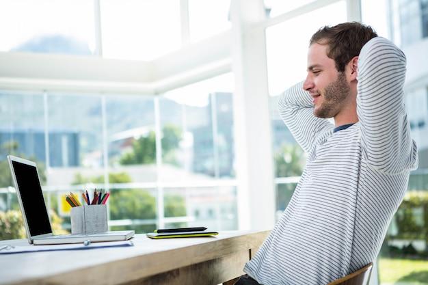 Uomo bello che si rilassa sulla sua sedia di scrittorio in un ufficio luminoso