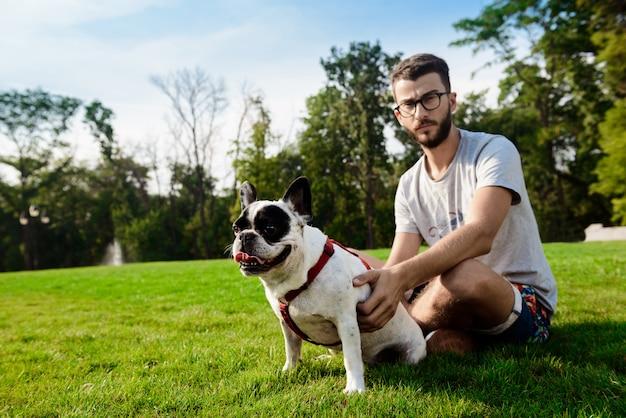 Uomo bello che si siede con il bulldog francese sull'erba in parco