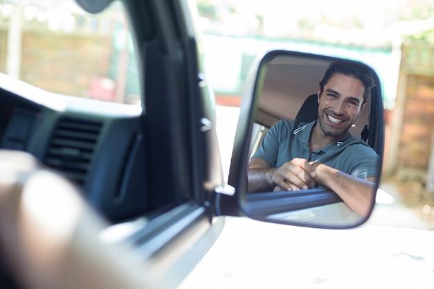 Uomo bello che si siede in automobile sullo specchio