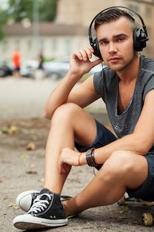Uomo bello che si siede in strada con le cuffie