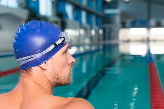 Uomo bello che si siede nella piscina
