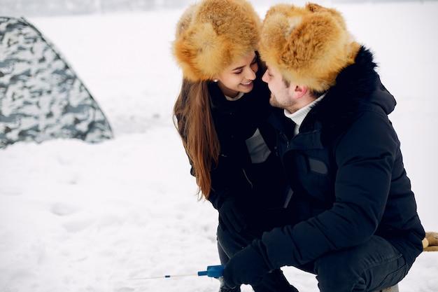 Uomo bello che si siede su una pesca di inverno con la moglie