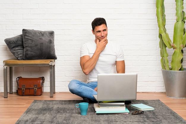 Uomo bello che si siede sul pavimento con il suo computer portatile che pensa un'idea