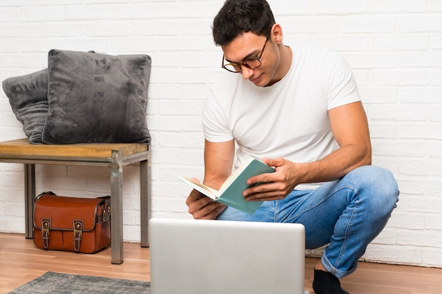Uomo bello che si siede sul pavimento con il suo computer portatile