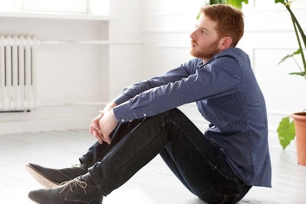 Uomo bello che si siede sul pavimento