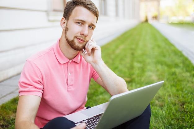 Uomo bello che si siede sull'erba nella città con un computer portatile e che parla sul telefono, ricerca di lavoro