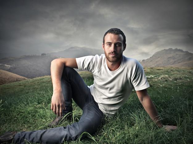 Uomo bello che si siede sull'erba