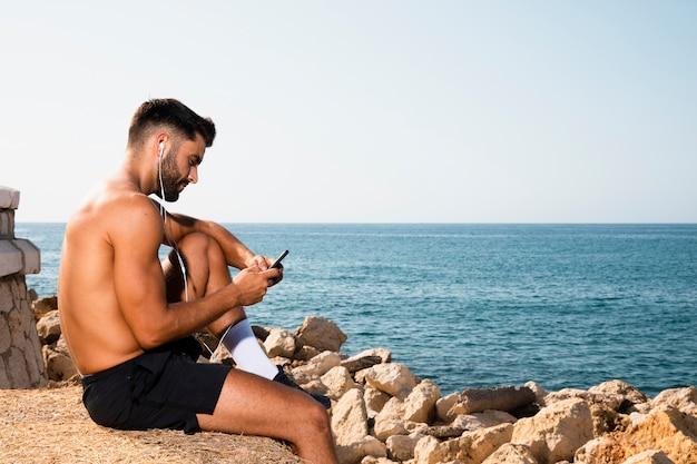 Uomo bello che si siede sulla spiaggia