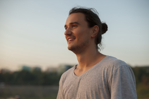 Uomo bello che sorride nel parco