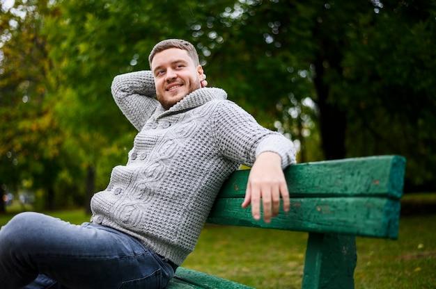 Uomo bello che sorride su un banco nel parco