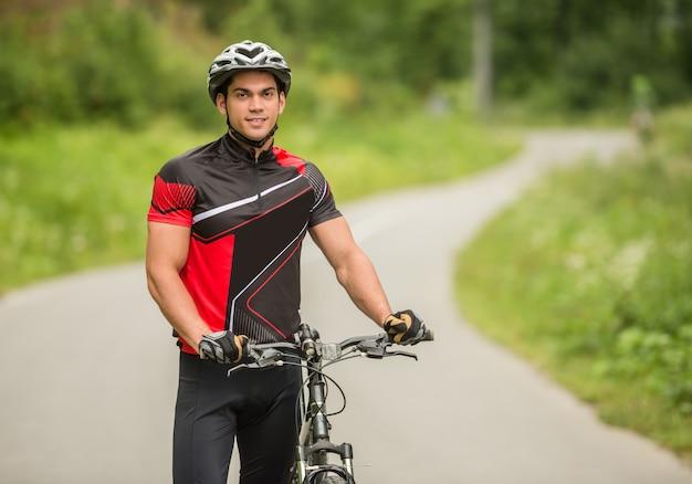 Uomo bello che sta con la sua bicicletta sul sentiero forestale.
