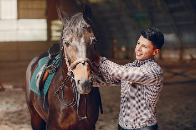 Uomo bello che sta in un ranch