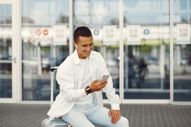 Uomo bello che sta vicino all'aeroporto