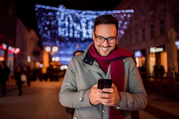 Uomo bello che texting alla via decorata della città alla notte. vista frontale.