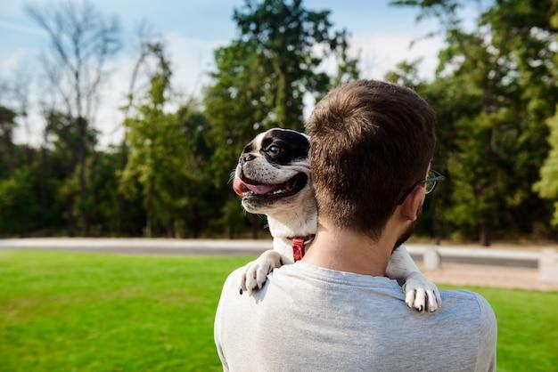 Uomo bello che tiene bulldog francese, camminando nel parco