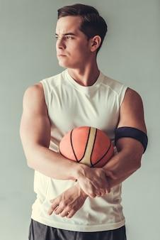 Uomo bello che tiene la palla da basket