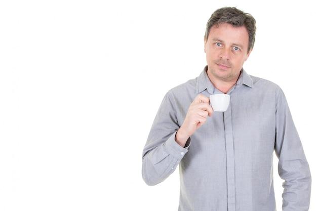 Uomo bello che tiene tazza con il tè del caffè con il fronte serio e il fondo bianco dello spazio della copia