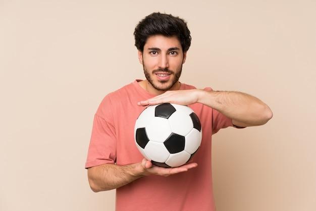 Uomo bello che tiene un pallone da calcio