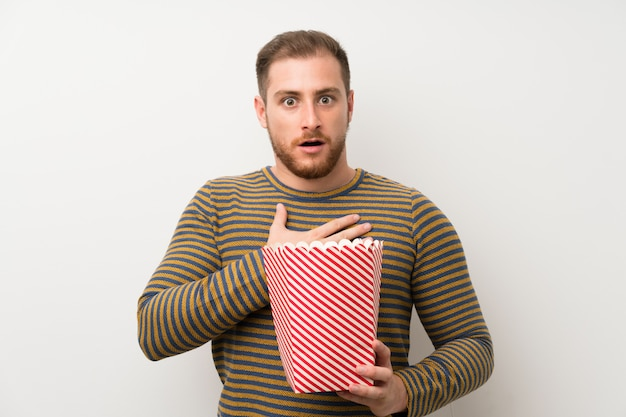 Uomo bello che tiene una ciotola di popcorn