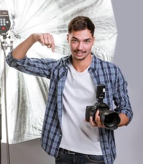 Uomo bello che tiene una macchina fotografica professionale