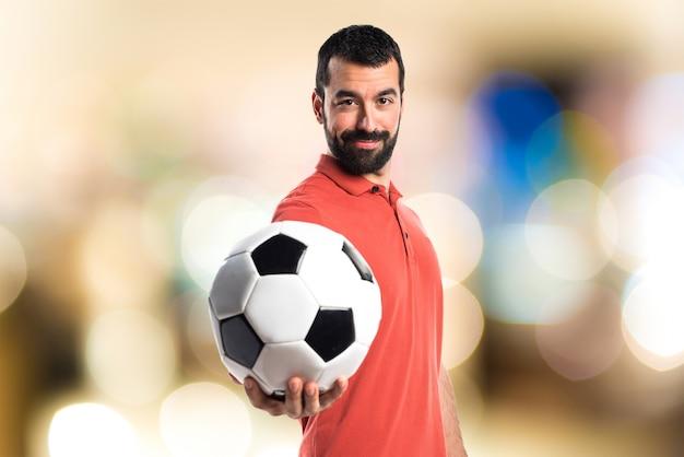 Uomo bello che tiene una pallina da calcio