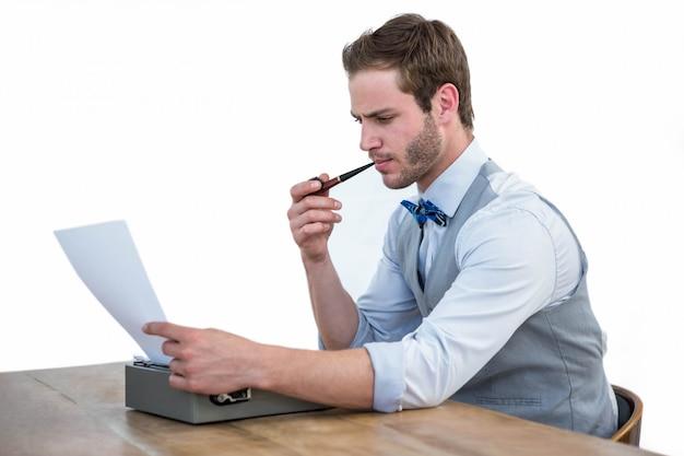 Uomo bello che usando macchina da scrivere antiquata