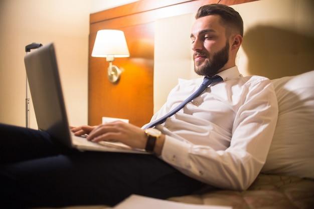 Uomo bello che utilizza computer portatile a letto