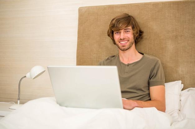 Uomo bello che utilizza computer portatile nel letto