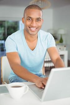 Uomo bello che utilizza computer portatile nella cucina