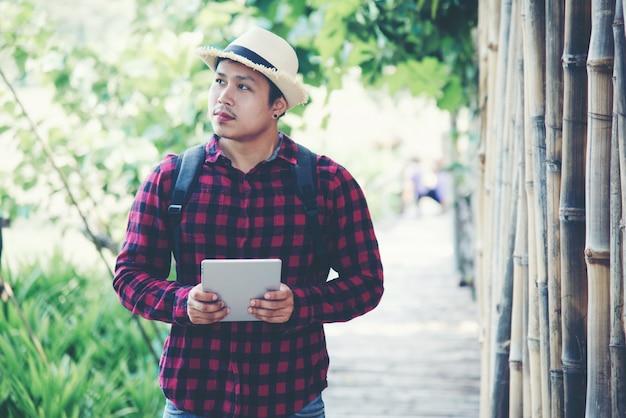 Uomo bello che utilizza computer portatile nella natura di viaggio