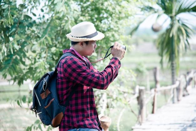 Uomo bello che utilizza la macchina fotografica nella natura di viaggio