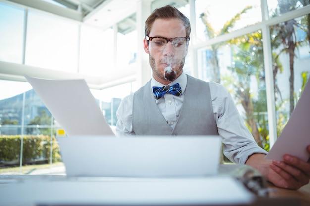 Uomo bello che utilizza macchina da scrivere antiquata nell'ufficio luminoso
