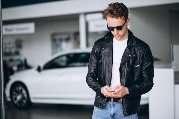 Uomo bello che utilizza telefono in una sala d'esposizione dell'automobile