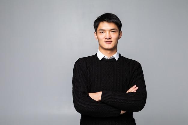 Uomo bello cinese che sorride e che ride isolato sulla parete bianca